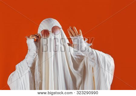 Happy Halloween. Cute Funny Ghost On A Bright Orange Background. Sheet Ghost Costume, Halloween Part