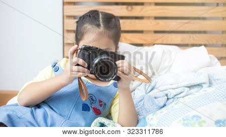 Little Girl Enjoying Take Photo With Camera In Room