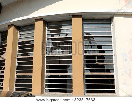 Many Big Windows With Glasses Completely Broken By Vandals And Iron Bars