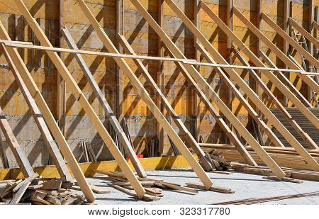 large and sturdy wooden supports on a construction site during the construction of the building poster