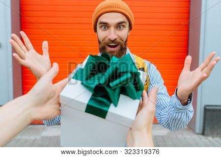 Wow. Unexpected news and a bright emotion, beard hipster man gets gift box on red background learned something unexpected and pleasant, he was surprised, delighted and joyful emotional reaction. poster