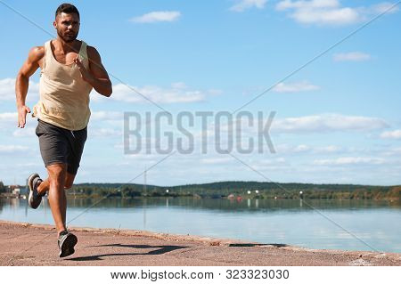 Strong Sport Man Jogging While Working Out Near City Riverfront