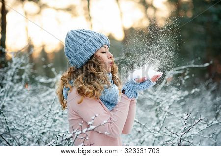 Beauty Winter Girl Blowing Snow In Frosty Winter Park. Outdoors. Flying Snowflakes. Sunny Day. Joyfu