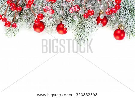 Christmas Concept. Xmas Border Composition With Red Glass Baubles, Holly Berries And Green Fir Branc