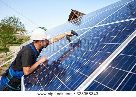 Technician Installing Solar Panel To Metal Platform Using Electrical Screwdriver On Blue Sky Copy Sp