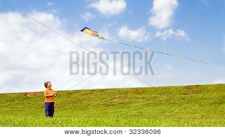Child flying kite and playing outdoors at park