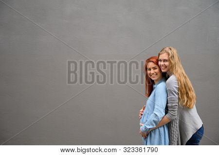 Same-sex Relationships. A Red-haired Pregnant Woman In A Denim Dress Is Standing Against A Gray Wall