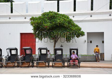 Kanchanaburi, Thailand, 09.09.2019: Rickshaws Or So-called Buggies Parking In Front Of A Beautiful T