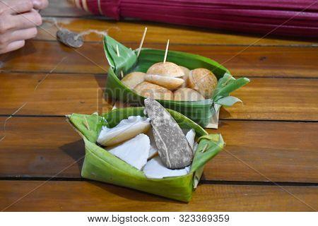 Thai Coconut-rice Pancakes Served In Folded Banana Leaves