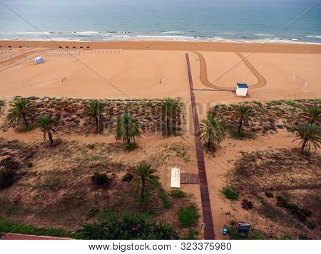 Aerial View Of A Mediterranean Beach, With A Cloudy Sky And White Sand. Drawings And Buildings In Th