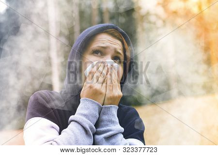 A Young Woman Choking In Burning Forest From Smoke, Covers Nose, Face With A Handkerchief From Fire.