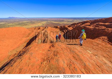 Uluru, Northern Territory, Australia - Aug 23, 2019: People Descend Along The Painted Guidelines Ove
