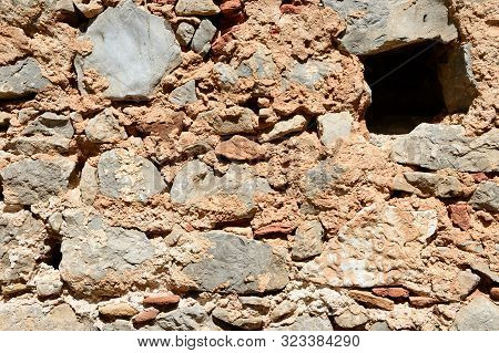 Fragment Of An Ancient Wall Illuminated By The Bright Sun Close-up. Stone Wall Background.