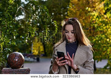 A Young Woman With Long Hair And In A Woolen Coat On A Walk In The Park On A Sunny Autumn Evening. A