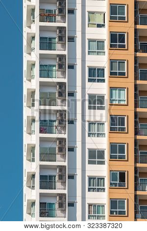 Facade of a modern residential building. Background texture of many balconies on high-rise apartment building in Ching Mai, Thailand