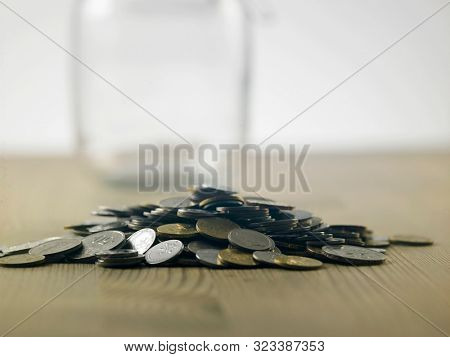 heap of coins and savings jar  on the wooden table