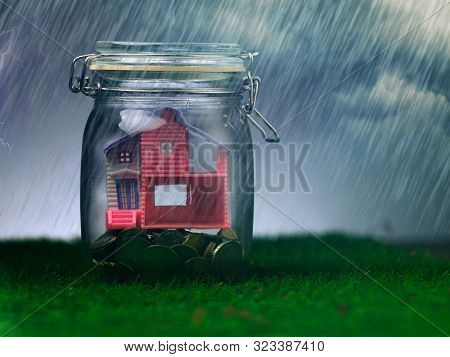model house and coins in glass jar, Protect a Property from the Weather