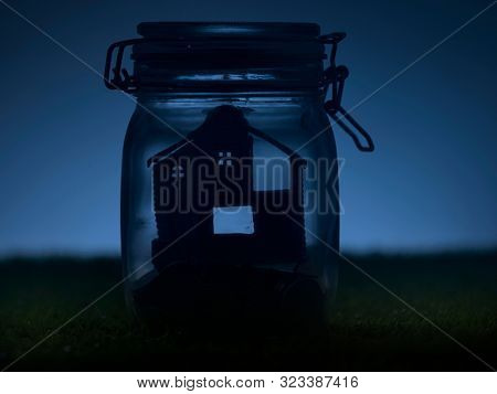 night scene of model house and coins in glass jar.