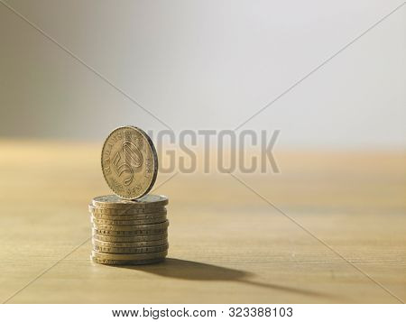 stack of malaysia currency coins on top of wood table