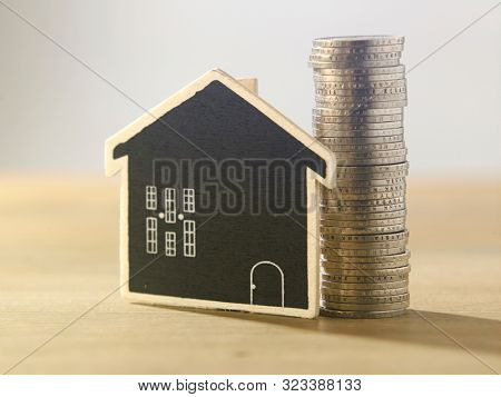 blackboard model house and stack of coins