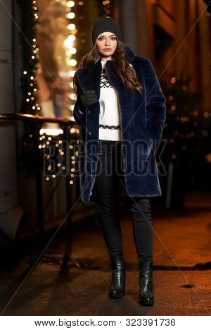 Pretty Girl In Blue Fur Coat Standing And Posing At Christmas Decorated City Street At Night. Beauti