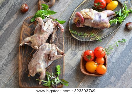 Wild Hunting Fowls In Cooking. Two Snipe Or Woodcock And A Partridge Lie On Wooden Rustic Board