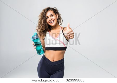 Portrait Of Cheerful Attractive Woman Showing Thumbs Up Gesture, With Bottle Of Water, At Fitness Cl