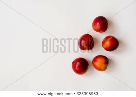 Fresh Organic Nectarines Lie On A White Background. Copy Space. The Concept Of Healthy And Healthy F