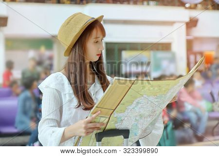 The Female Tourist Uses Her Hands To Open The Tourist Map To See Route Inside The Railway Station