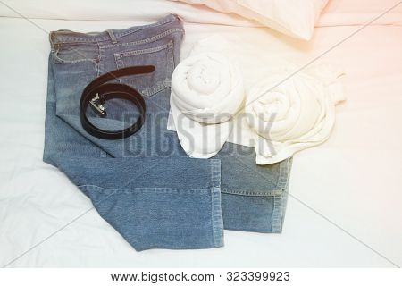 Jeans And Belt  Place On The Bed  And 2 White Towels In The Room
