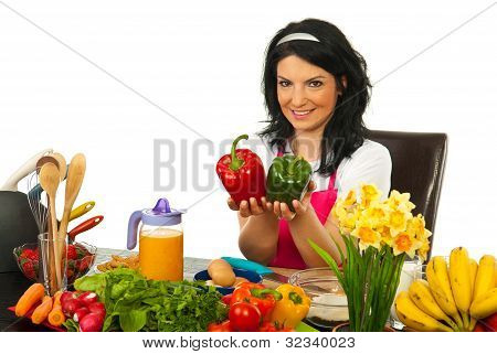 Happy Woman In Kitchen Showing Peppers