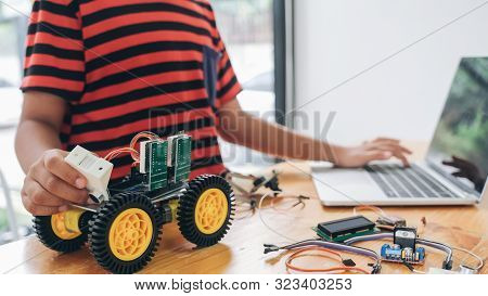 Boy With Tablet Pc Computer Programming Electric Toys And Building Robots.