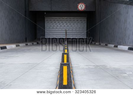 Access To Underground Garage With Roller-shutter Door And Road Dividers With Yellow Sticks