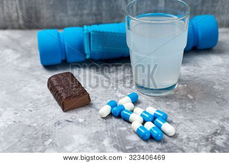 High Protein Bar, Bcaa (amino Acids) Drink, Creatine Capsules And Blue Dumbbell In Background. Sport