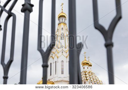 White christian church with gilt domes seen through defocused black wrought fence poster
