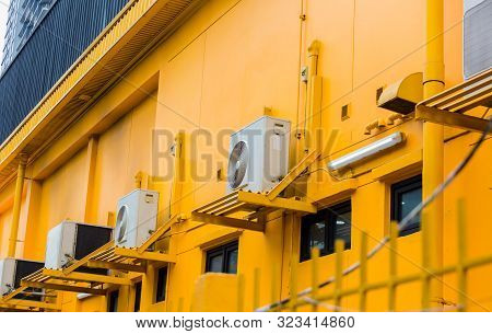 Air Conditioning Compressor With Black Glass Windows On The Yellow Wall Building Background.