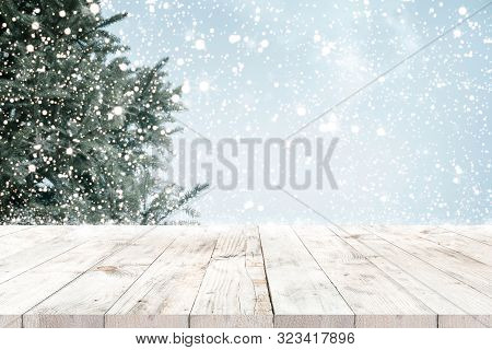 Top Of Empty Wood Table With Fir Tree And Snowfall  Backdrop. Ready For Your Product Display Or Mont