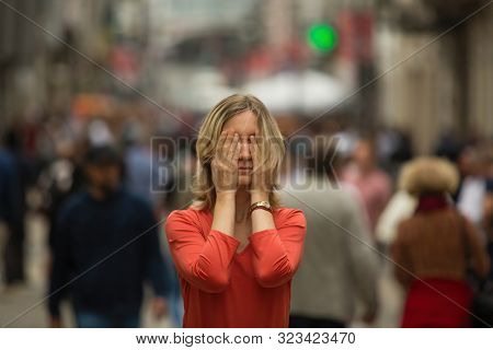 Panic attack in public place. Young woman covers his eyes with hands at standing in the middle of a busy street.