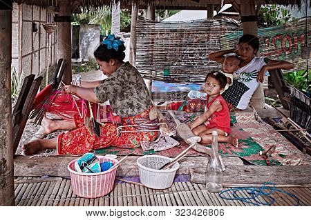 Bali, Indonesia - Sep 21, 2019: Weaver woman behind a loom, handmade manufacturing fabric and carpets. Handmade on a wooden loom manufacturer of thread, fabric and carpets.