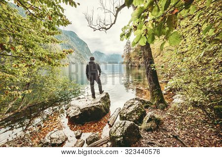 A Man Stands On Rock And Looking At The Wonderful Autumn Lake, Seasonal Landscape, Koenigsee, Deutsc