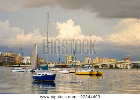 Boats In Harbor Under Cloudy Skies