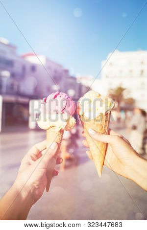 Womans Hands Holding Ice Cream In Waffle Cones. Strawberry And Mango Ice Cream.