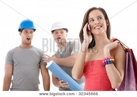 Builder workers watching attractive woman walking by, on mobile phone call with shopping bags, smiling. Isolated on white.