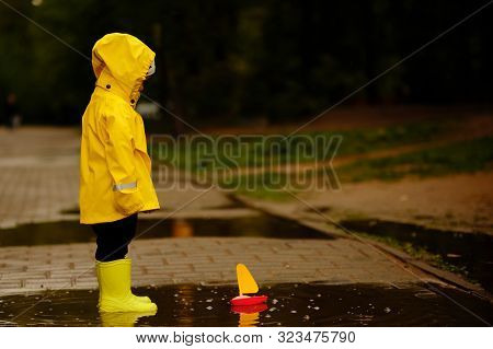 Boy In A Yellow Raincoat Looks At A Toy Ship That Floats In A Puddle. Little Baby Walking In The Par
