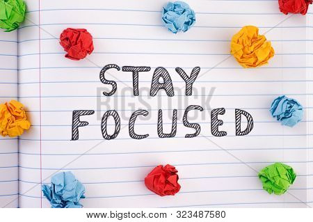 Stay Focused. Phrase Stay Focused On Notebook Sheet With Some Colorful Crumpled Paper Balls Around I