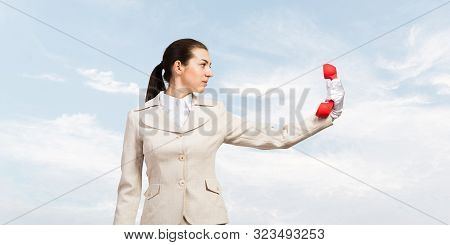 Businesswoman Holds Vintage Red Phone On Distance. Serious Operator In Business Suit Posing With Tel