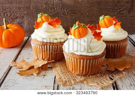 Fall Pumpkin Spice Cupcakes With Creamy Frosting And Autumn Toppings. Close Up Against A Rustic Wood