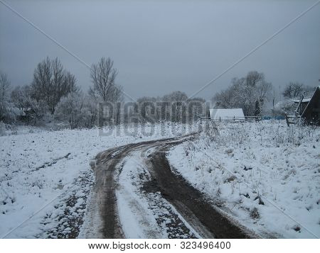 Muddy Dirt Road In An Old Abandoned Village On A Cloudy Winter Day. The Road Was Muddy And Impassabl