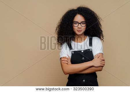 Photo Of Beautiful Dark Skinned Teenage Girl Poses With Arms Crossed, Wears Spectacles, White T Shir
