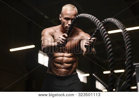 Fitness Athletes Training Using Battle Ropes Intense Workout Team Exercise Challenge In Gym Enjoying